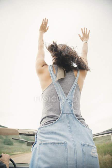 Femme debout avec les bras levés — Photo de stock