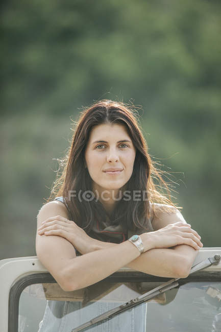 Mujer sonriendo apoyada en frente de la máquina - foto de stock