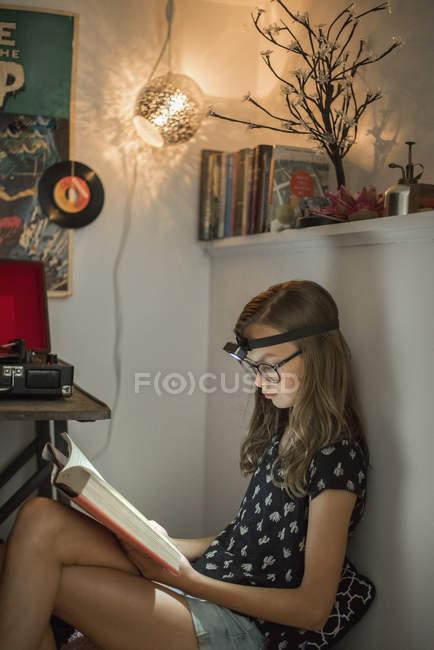 Girl reading book in glasses — Stock Photo