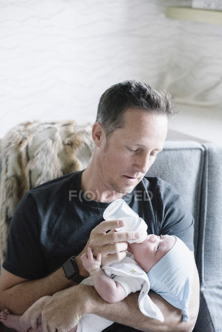 Padre acunando a un bebé pequeño - foto de stock