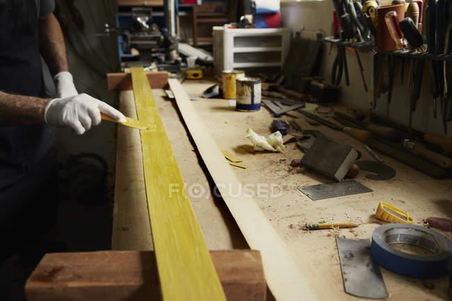Mann untersucht Stück Holz — Stockfoto