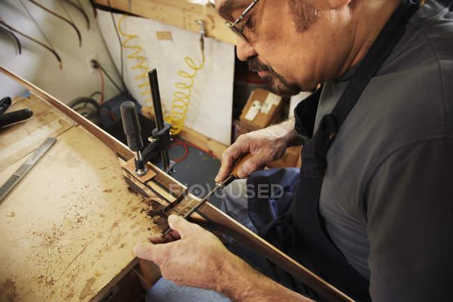 Uomo che fa arco in officina — Foto stock
