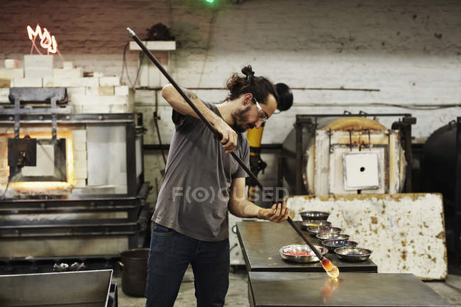 Glassblower holding of molten glass — Stock Photo