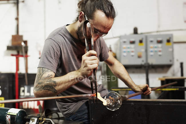 Glassblower working on piece of glass — Stock Photo