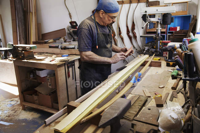 Man working on wooden bow — Stock Photo