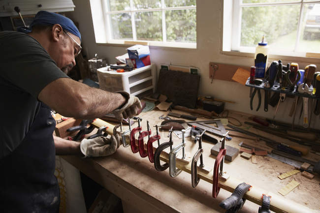 Man working on wooden bow in workshop — Stock Photo