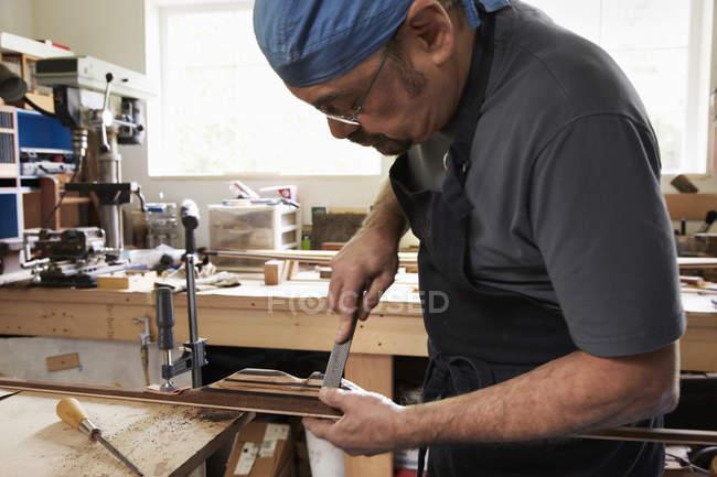 Людина, що працює над дерев'яний лук — стокове фото