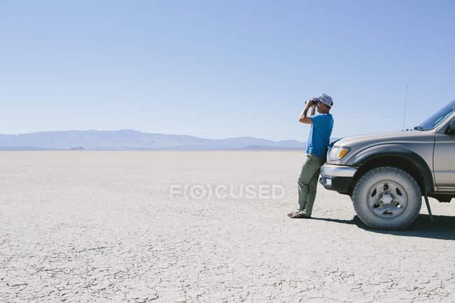 Hombre de pie en el inmenso desierto - foto de stock