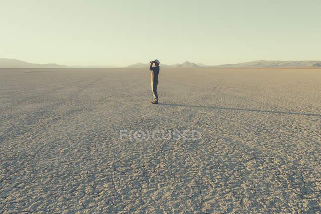 Человек, стоящий в удаленной пустыне — стоковое фото