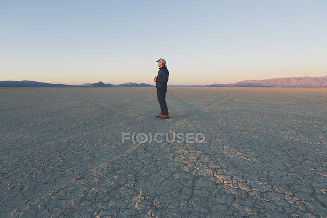 Man standing in vast desert playa — Stock Photo