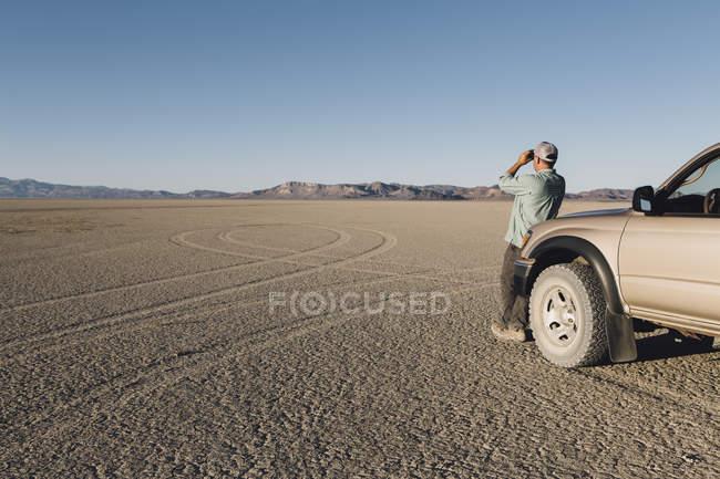 Hombre mirando a través de binoculares en el desierto - foto de stock