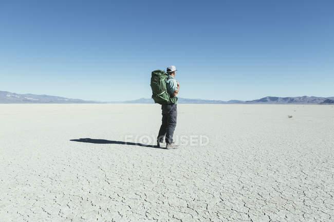 Male backpacker hiking in vast desert — Stock Photo