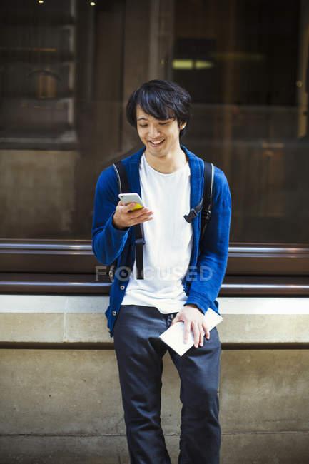Giovane giapponese uomo utilizzando smartphone — Foto stock