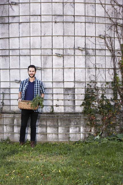 Юнак стоячи з кошиком рослин — стокове фото