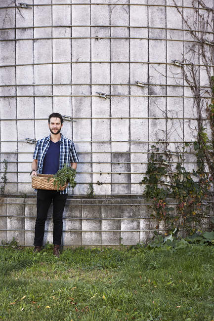 Young man standing with basket of plants — Stock Photo