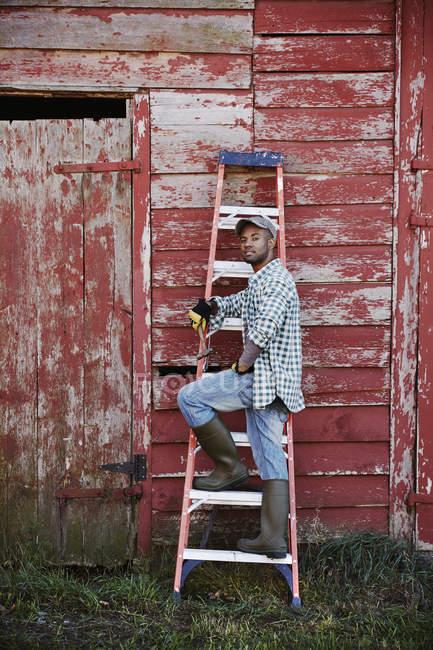 Jovem de pé perto do celeiro — Fotografia de Stock