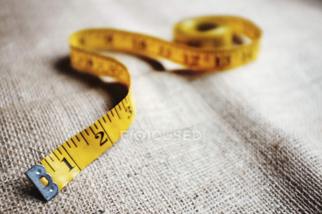 Tape measure lying on fabric — Stock Photo