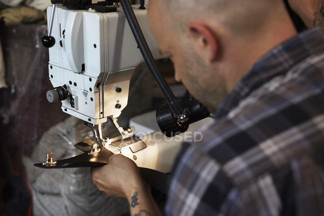 Man working on industriall sewing machine — Stock Photo