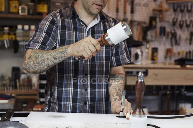 Craftsman at leather workshop — Stock Photo