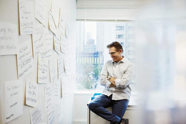 Чоловік, спираючись на столі в офісі — стокове фото