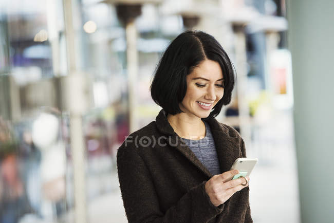 Mujer sosteniendo teléfono celular - foto de stock