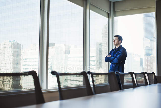 L'uomo in piedi e guardando fuori della finestra — Foto stock
