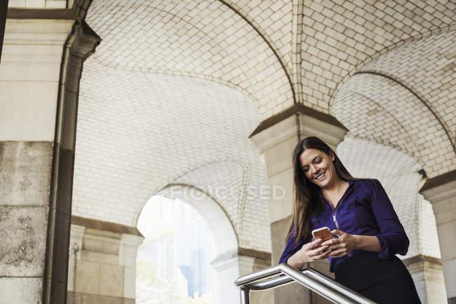 Жінка, стоячи і перевірка мобільного телефону — стокове фото
