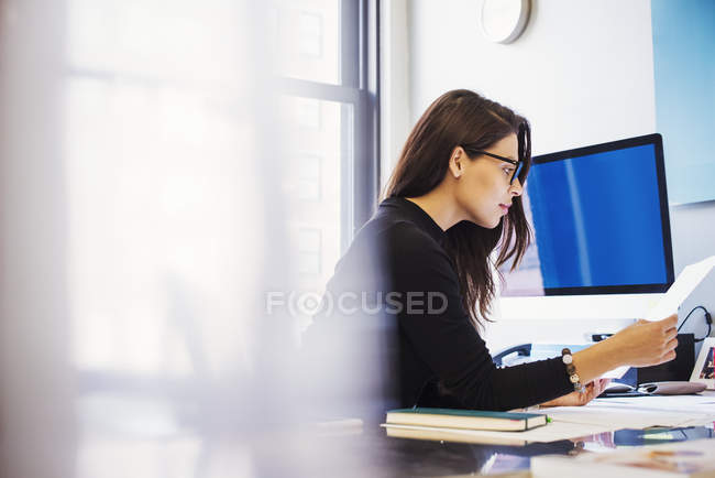 Woman sitting at desk in office — Stock Photo