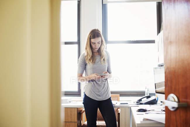 Жінка, стоячи в офісі — стокове фото