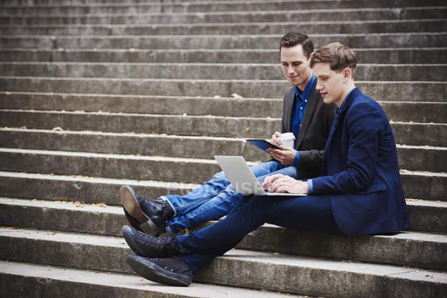 Hombres sentados en escalones - foto de stock