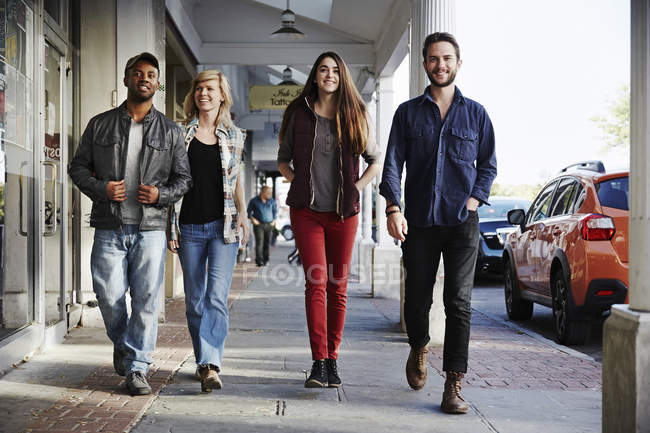 Men and women walking along sidewalk — Stock Photo