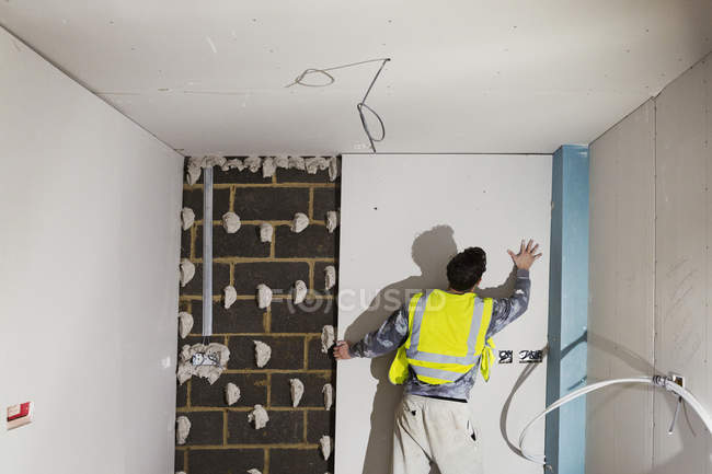Building worker fitting plasterboard — Stock Photo