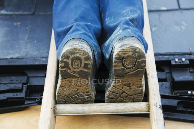 Человек, стоящий на лестнице на крышу уровня — стоковое фото