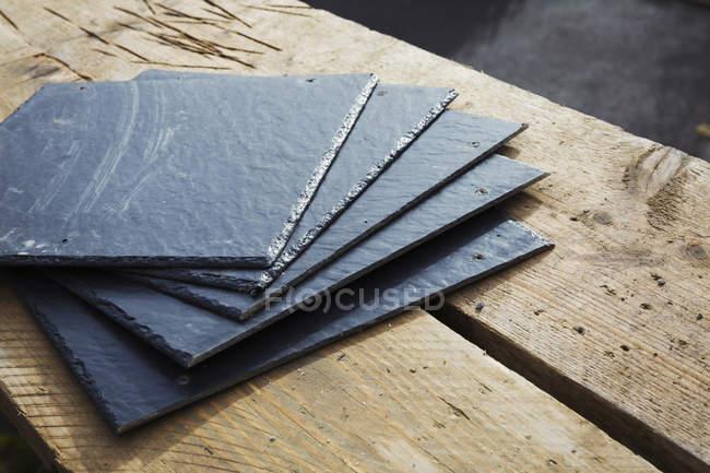 Telhas de ardósia em uma superfície de madeira — Fotografia de Stock