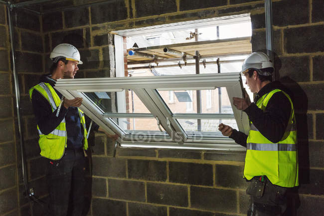 Two builders fitting window frame. — Stock Photo