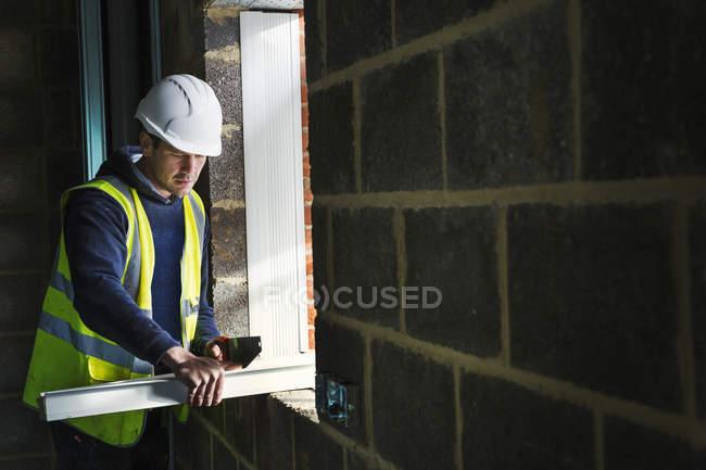 Construtor em chapéu duro usando serra — Fotografia de Stock