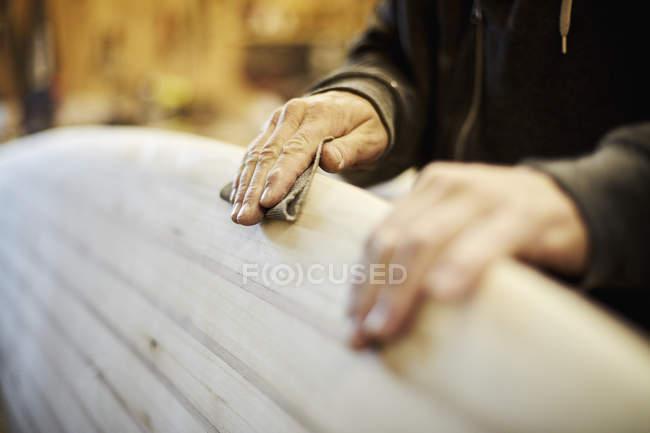 Man sanding edge of wooden surfboard. — Stock Photo