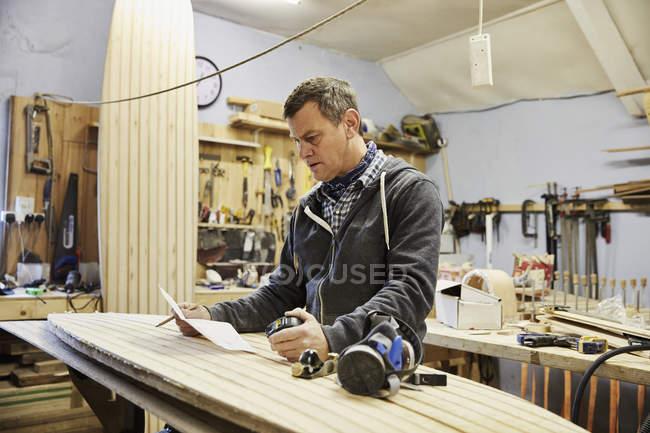 Man in surfboard workshop — Stock Photo