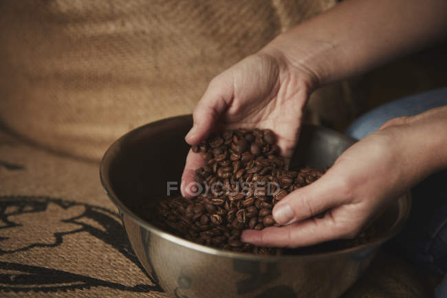 Person holding fresh roasted beans — Stock Photo