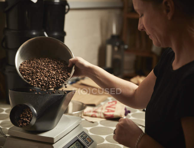 Person pouring coffee beans into grinder. — Stock Photo