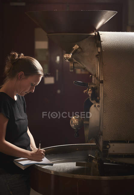 Woman  testing roasted coffee beans. — Stock Photo
