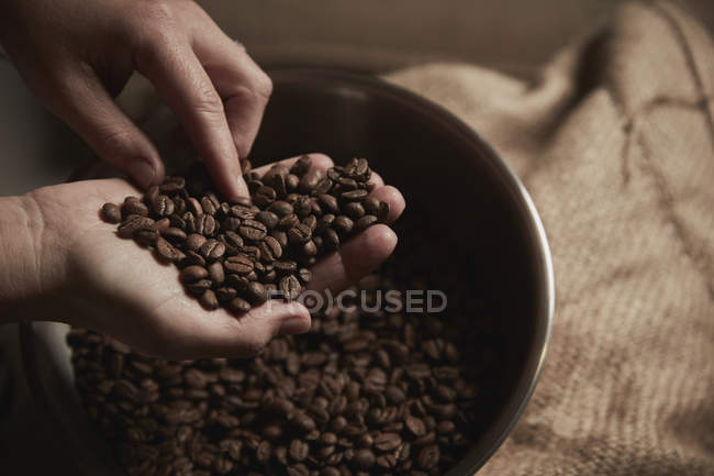 Person holding handful of coffee beans — Stock Photo