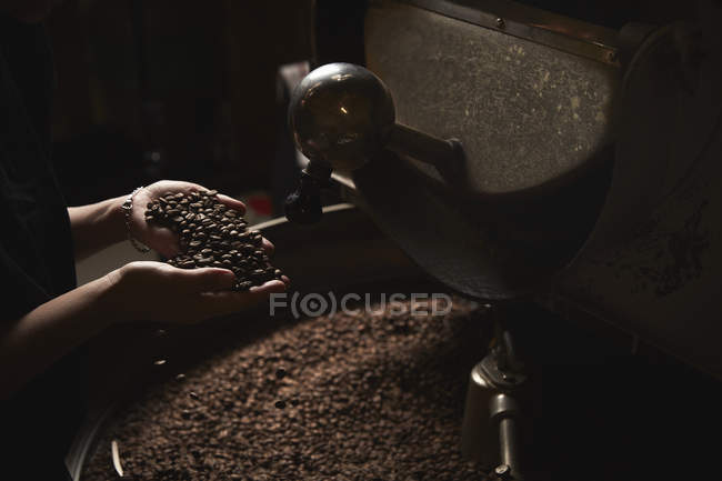 Person holding handful of fresh roasted beans — Stock Photo