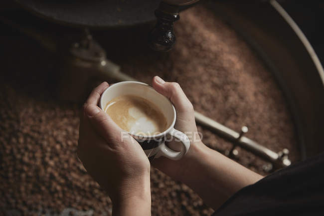 Person holding fresh brewed cup — Stock Photo