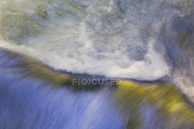 Вода течет через валун — стоковое фото