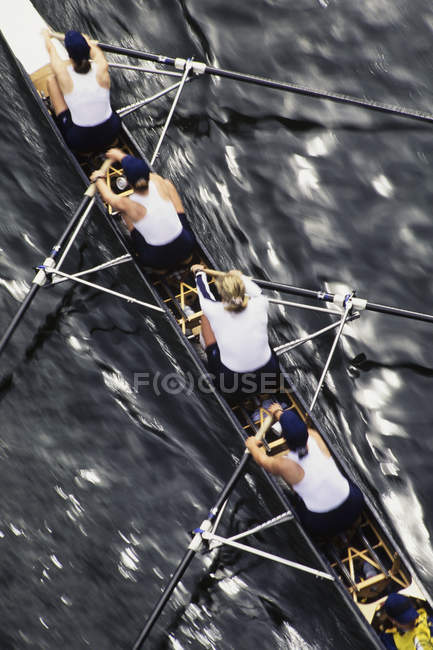 Female rowing crew in racing shell — Stock Photo