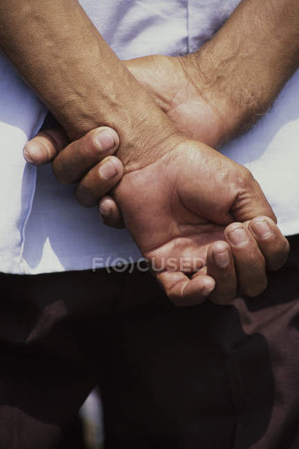 Hands clasped behind back. — Stock Photo