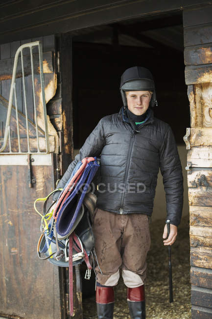 Man in helmet and carrying riding gear — Stock Photo