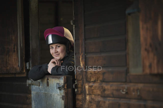 Woman standing in box stall in stable — Stock Photo