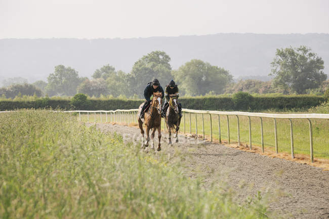 Two horses and riders on gallops path — Stock Photo